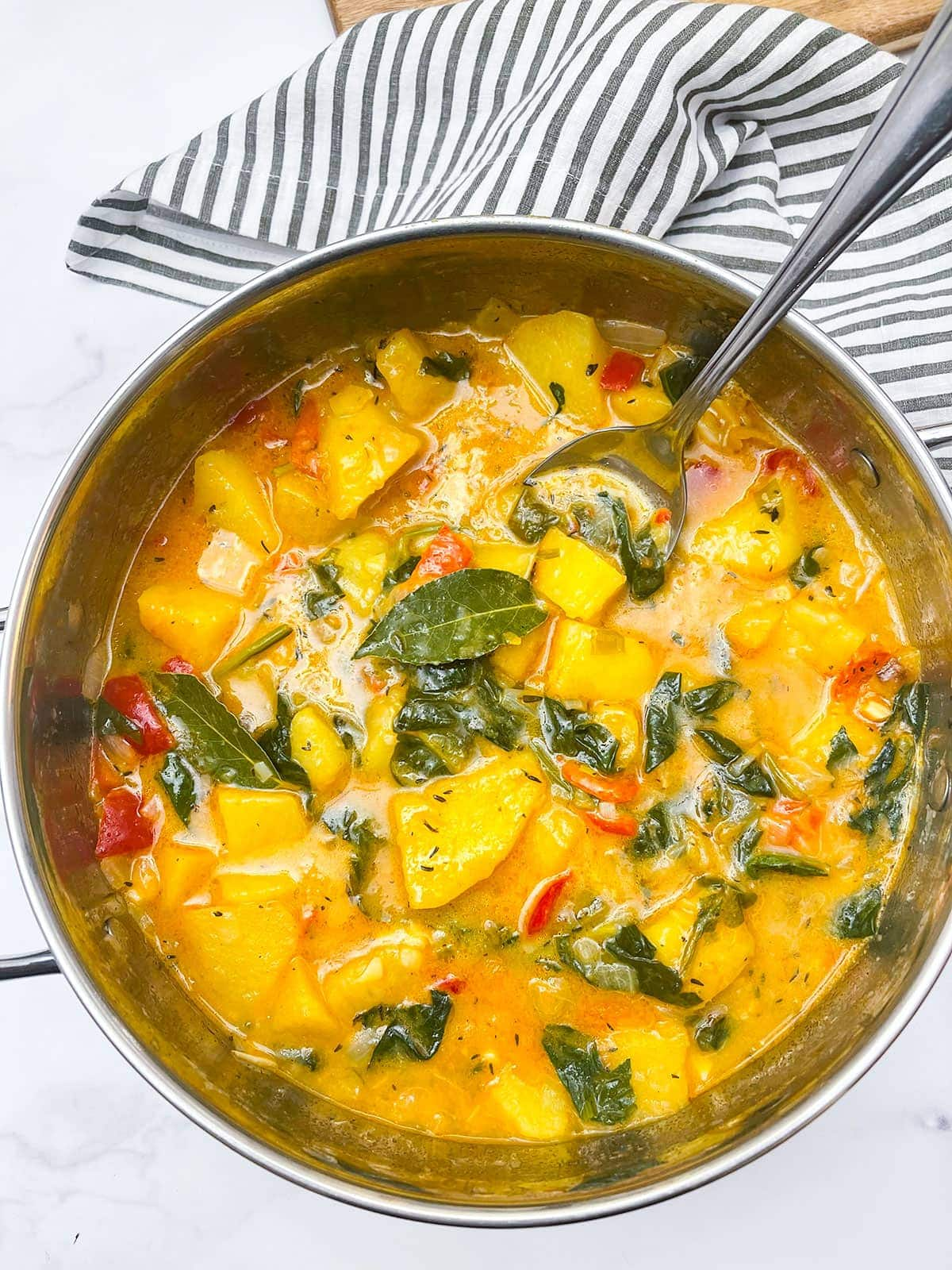 yellow yam stew in a saucepan on a white background with black and white stripe napkin