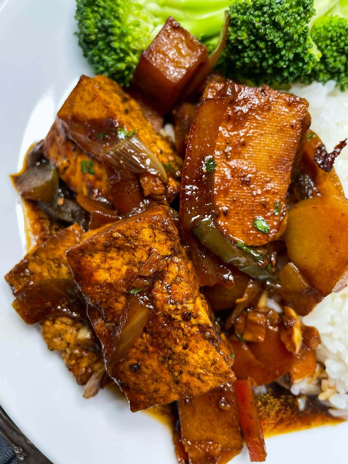 Jamaican vegan brown stew chicken on a white plate with broccoli