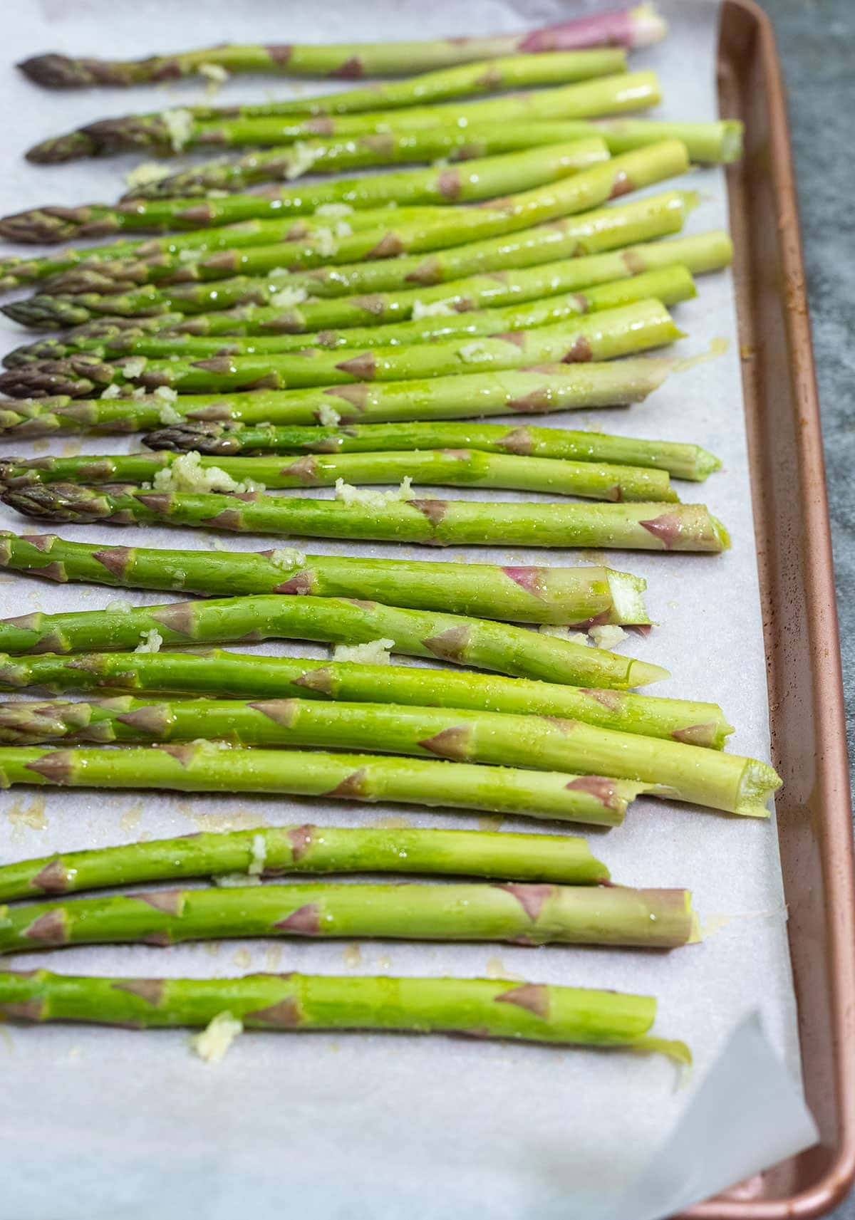 seasoned asparagus on a baking tray with minced garlic