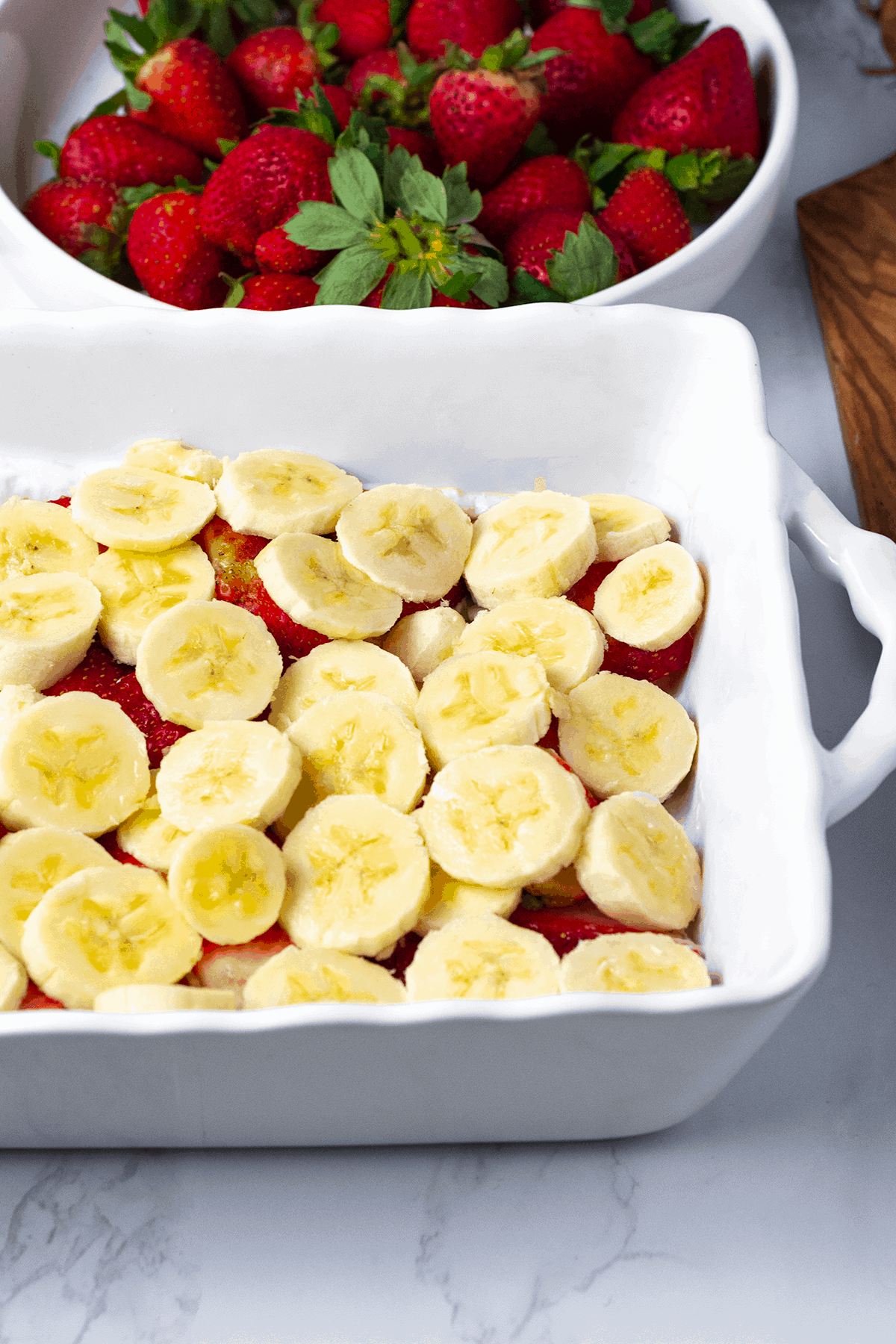 Gluten-Free Vegan Strawberry Ice Box Cake being layered in a white casserole dish with strawberries and bananas
