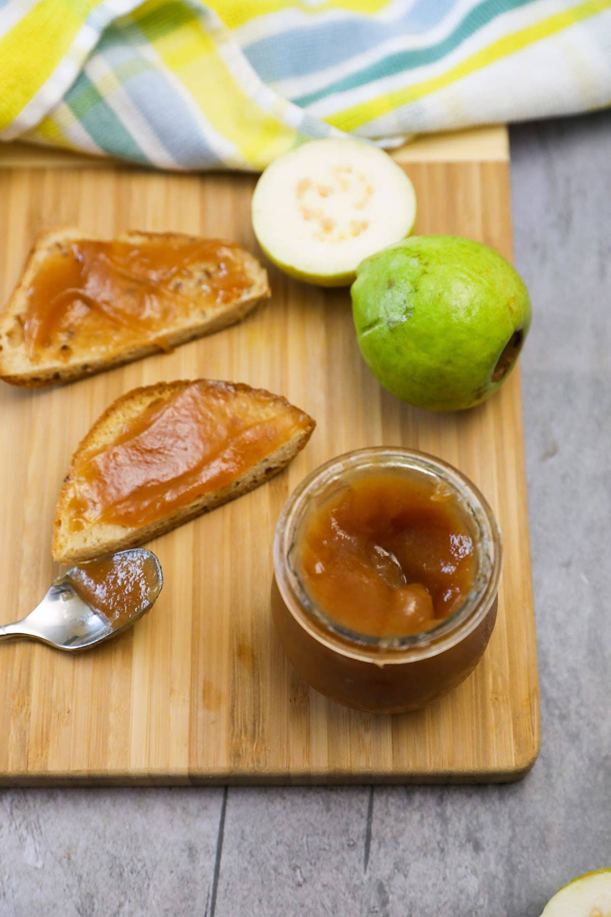 overlay guava jam on cutting board in a jar and on toasts