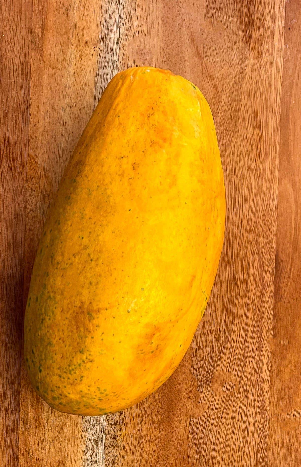 whole papaya fruit on a wooden background
