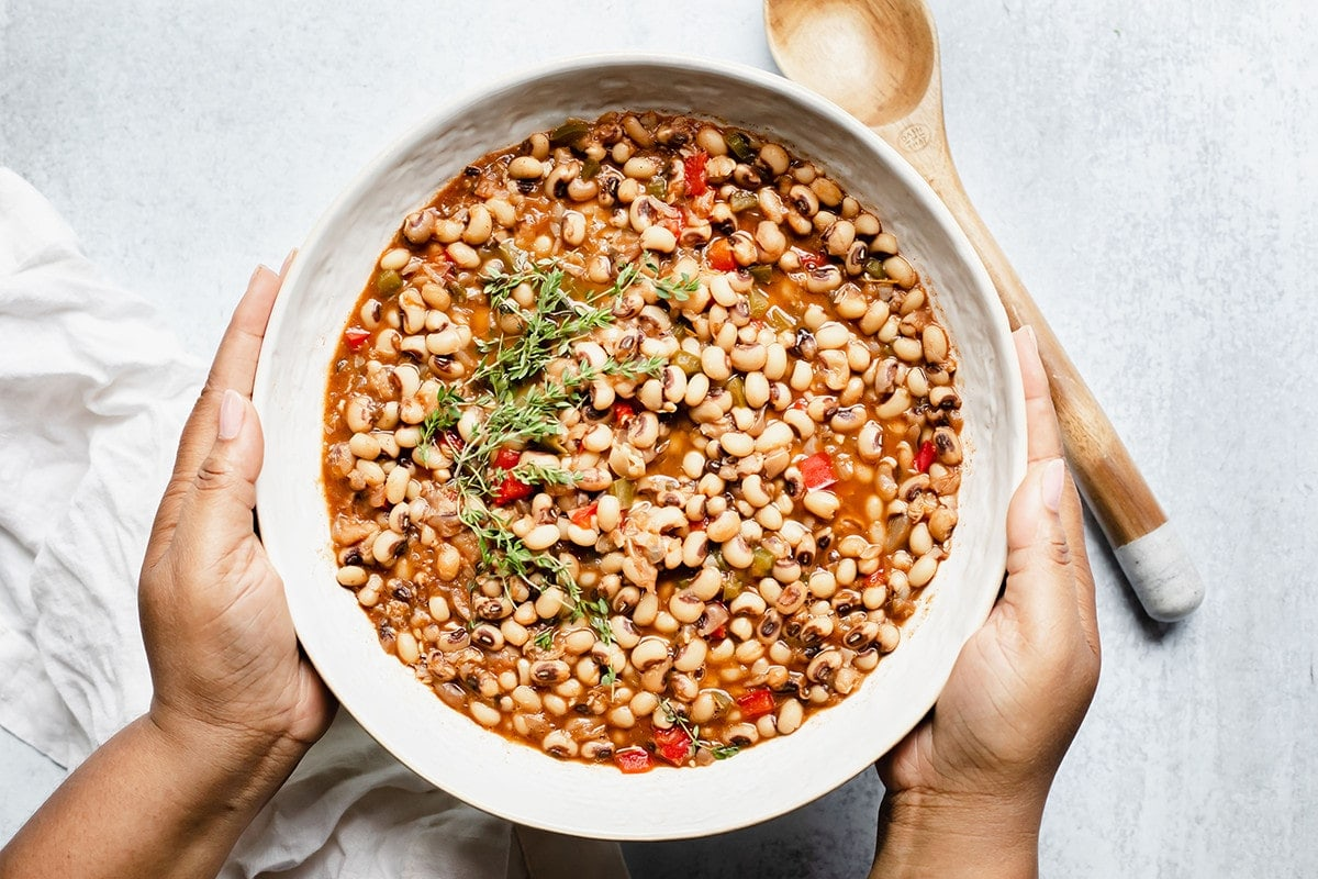 overlay southern black-eyed peas in a white bowl with a wooden spoon, being held with hands on a white background