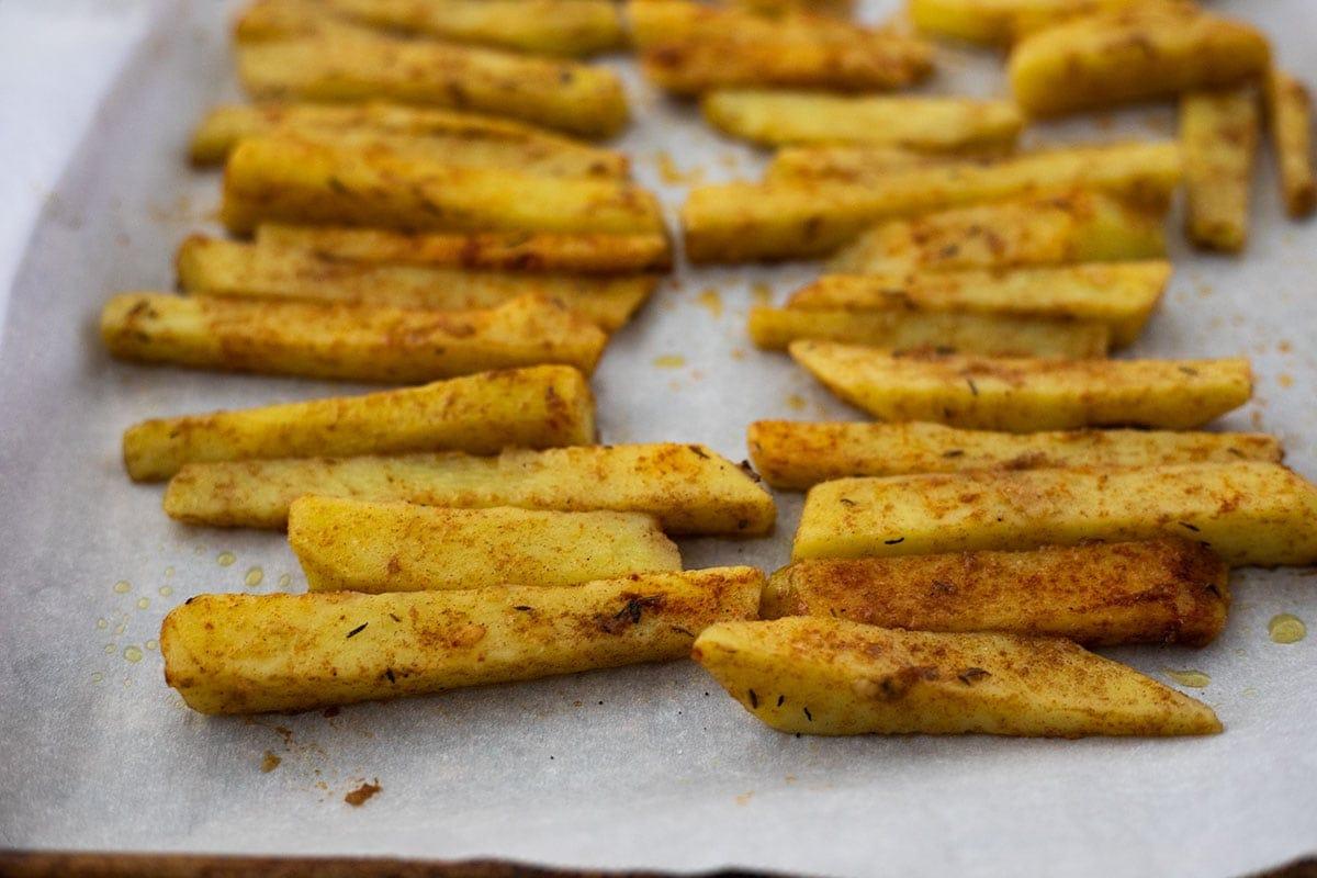 seasoned yellow yam fries on baking sheet