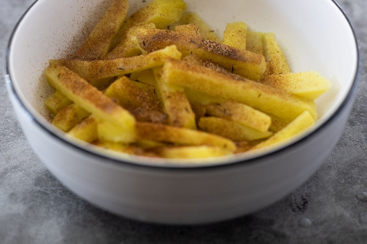 seasoned yellow yam fries in a white bowl