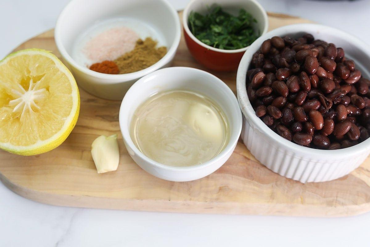 ingredients for black bean hummus, black beans, tahini, lemon juice, parsley, spices. garlic