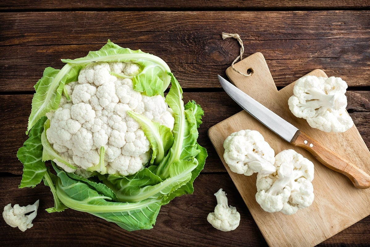 cauliflower whole and florets on a wooden cutting board
