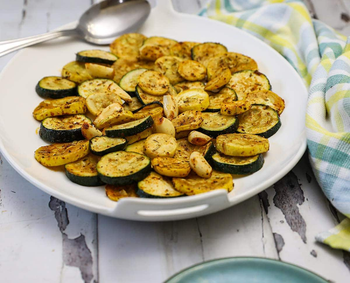 oven roasted zucchini and yellow squash on a white platter on a white background