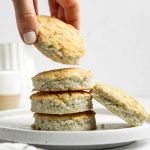 Hand taking one from a stack of coconut flour biscuits on small white plate