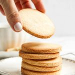 Hand picking up keto sugar cookie made with coconut flour from a stack