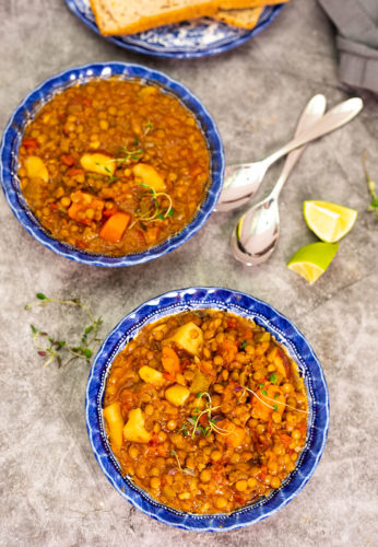 Overlay lentil stew in two blue bowls with two spoons, lime wedges on a grey background
