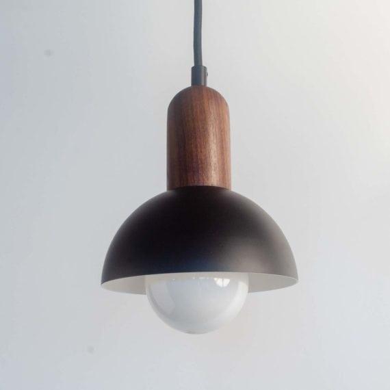 hemisphere pendant light with black cord, walnut top, and black metal hemisphere shade with white interior