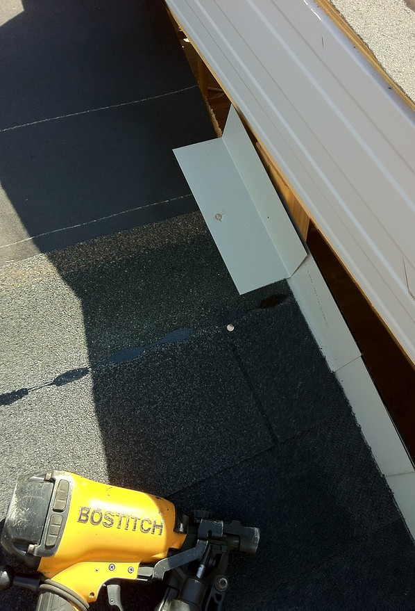 How to install metal step flashing on courses of shingles against vertical wall