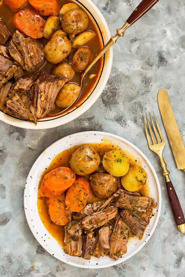 Plate and bowl of slow cooker pot roast with carrots and potatoes