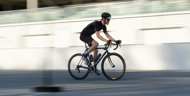 Cyclist riding fast as the background blurs