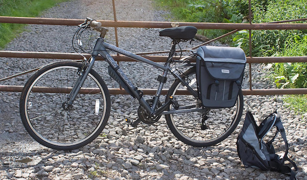 Hybrid bike parked against a rusty gate