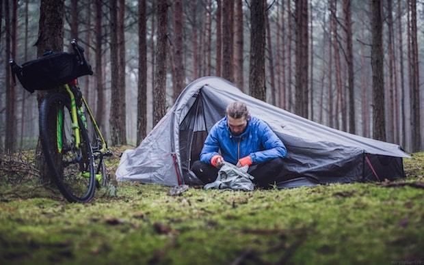 Cyclist takes a break in a wet campsite