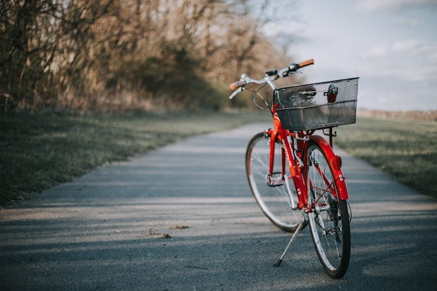 Bike standing up right on its kickstand on a beautiful country bike path
