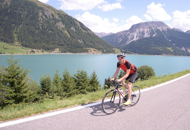 A road cyclist on a paved road alongside a lake in the mountains