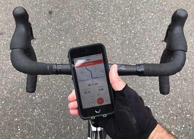 Cyclist holding an iphone above his bike handlebars