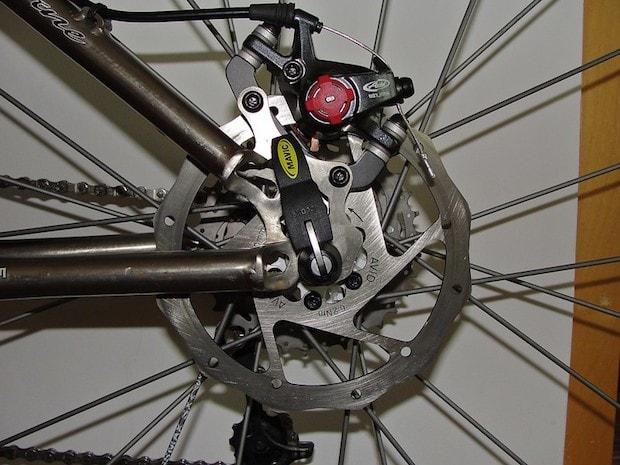 Closeup of a bike's rear disc brake that looks like it has been freshly cleaned of rust