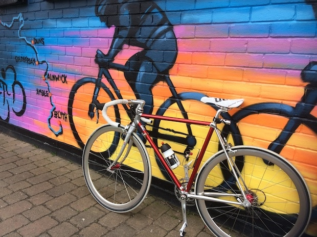 Bike with a traditional frame leaning against a wall mural showing other traditional bikes