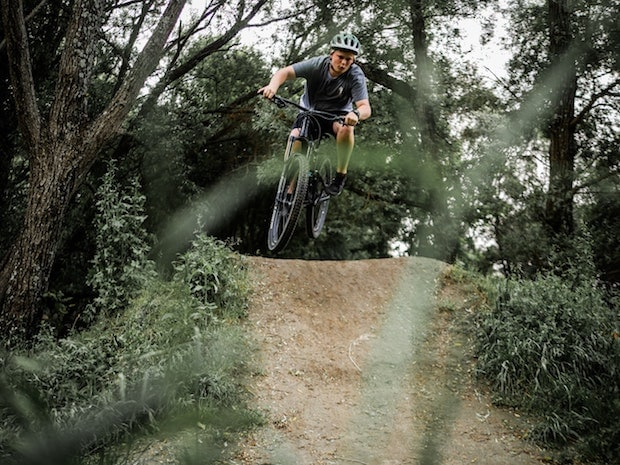 A mountain biker coming over a bump on a trail