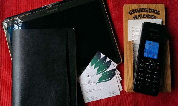 Hilfsmittel für die Kontaktpflege im Netzwerk-Marketing: Tablet, Adressbuch, Visitenkarten, Geburtstagskalender, Telefon