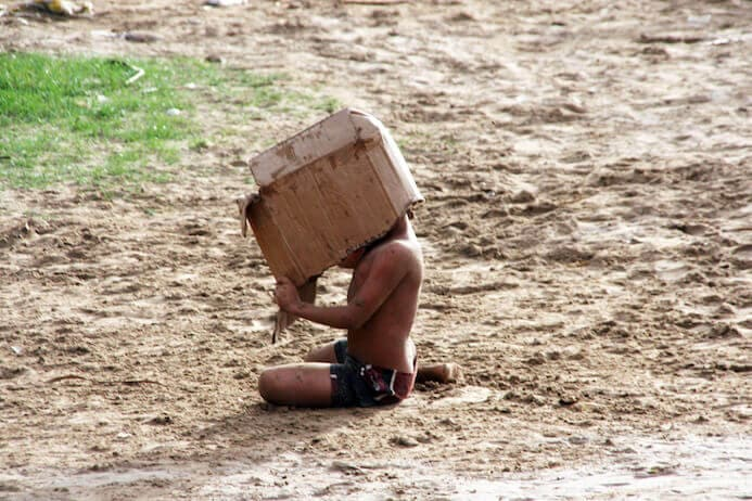 photography portfolio tips - child playing with a box on the sand in Venezuela