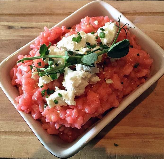 A dish of beetroot risotto and goat's cheese.