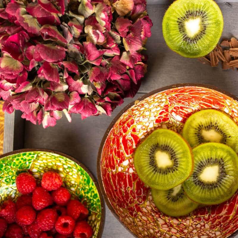 Zwei Kokosnussschalen die Früchte enthalten und eine Blume auf einem Tisch