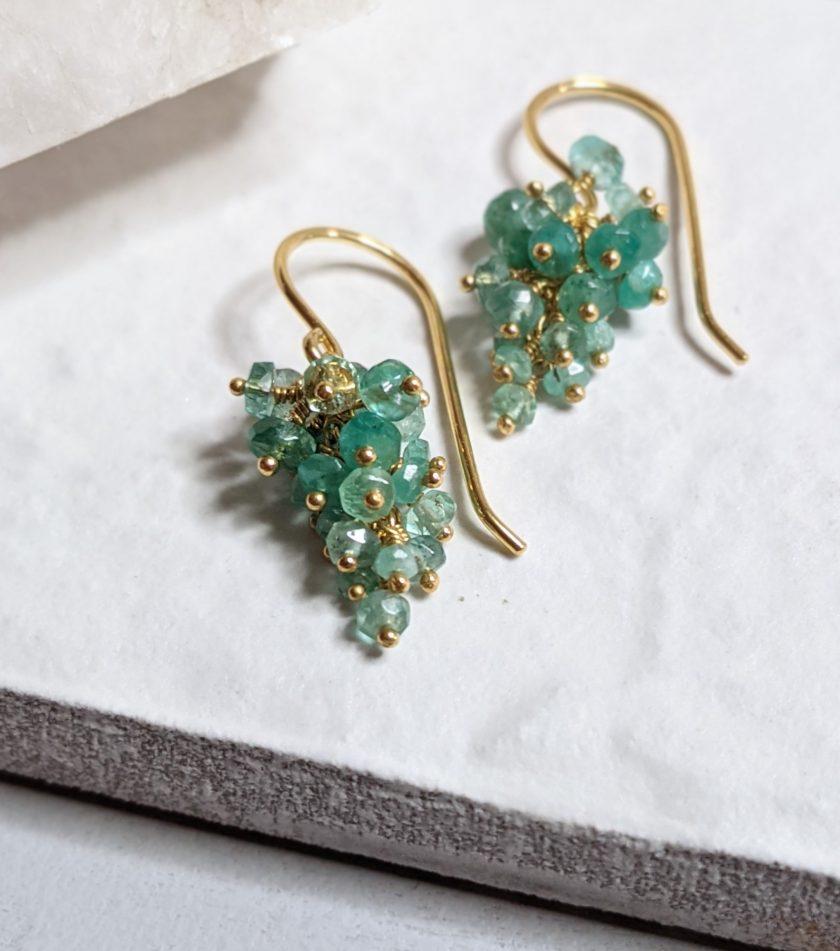 Green emerald earrings on a white tile