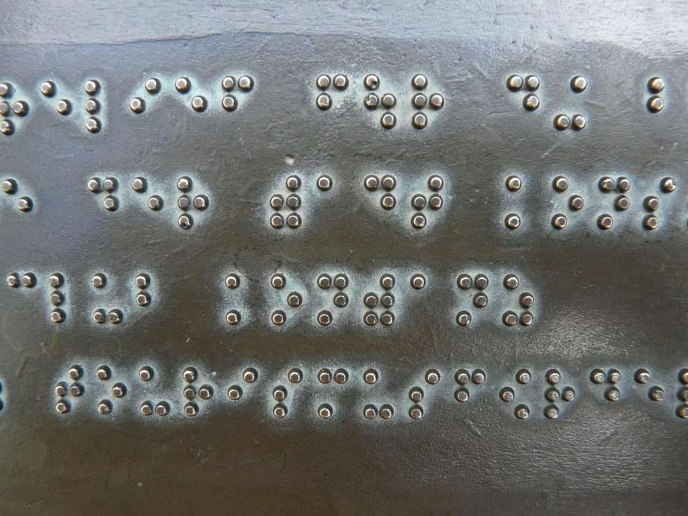 Braille letters on a metal sheet for our language spotlight.