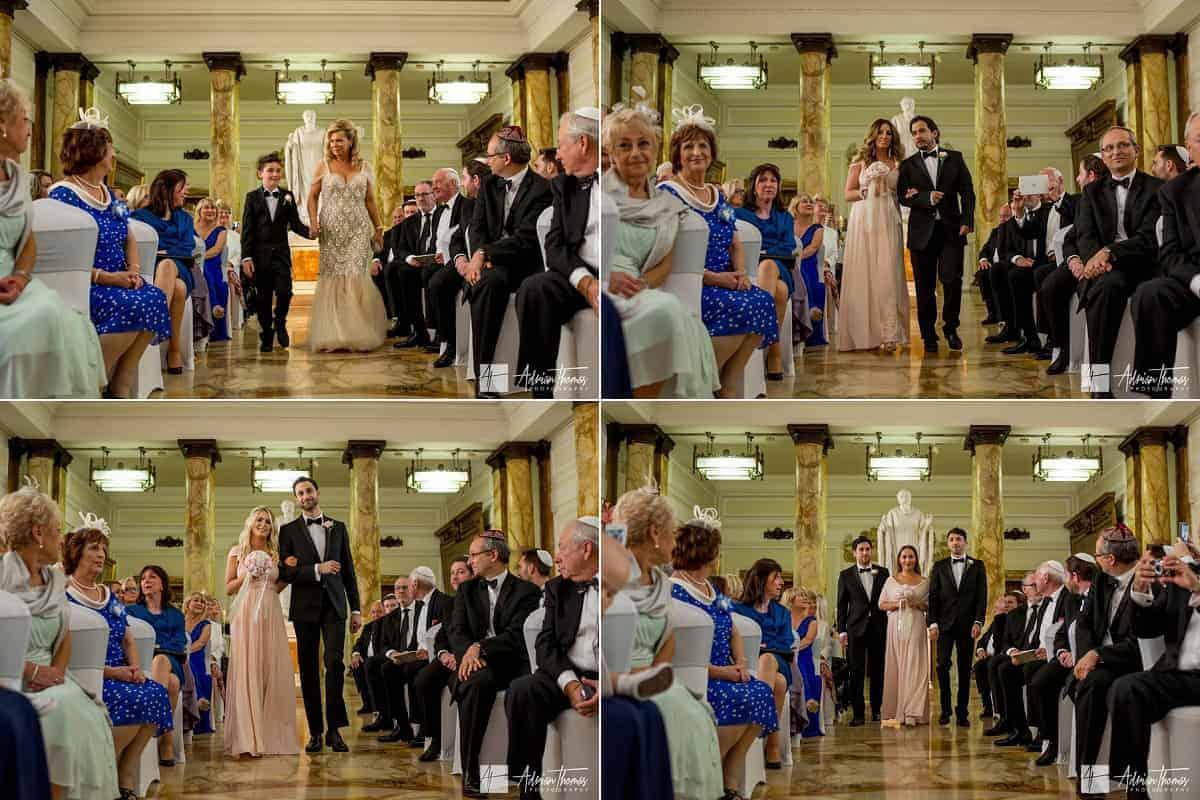 Bridesmaids walking down aisle towards groom and Chuppah.