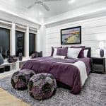 purple and grey beach-style bedroom with fluffy rug and ottomans