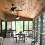 a rustic porch with tongue and groove ceiling from stained knotty material