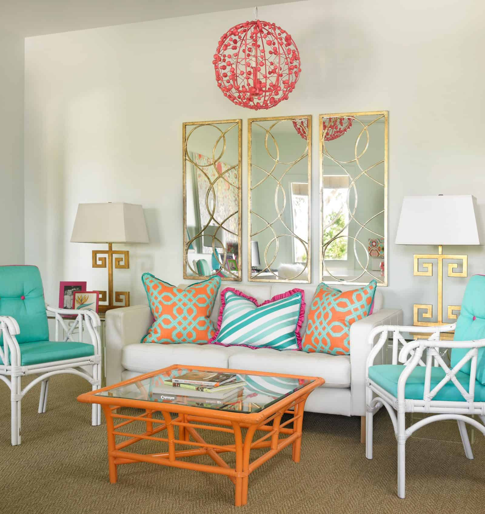 a contemporary living room with turquoise chairs and gold mirror