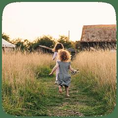 girls running down grass path