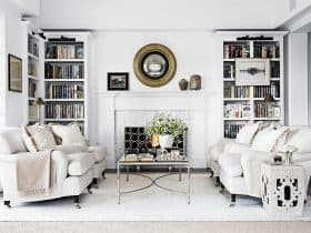 elegant and luxurious design of a classic, traditional white fireplace with custom white bookshelves surrounding it