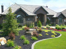 a beautiful combination of lawn, black lava rock, and decorative plants