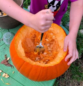 child scooping out a pumpkin