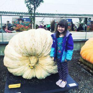 child next to giant white pumpkin