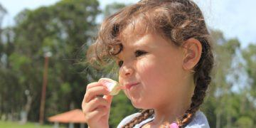 Keeping kids healthy and well-fed on vacation is a challenge; girl eating sweets outdoors