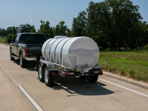 Truck Hauling 1000 Gallon Water Trailer On A Road