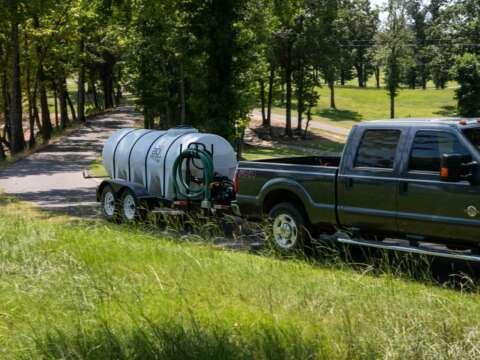 Truck Hauling 1000 Gallon Water Trailer on Driveway