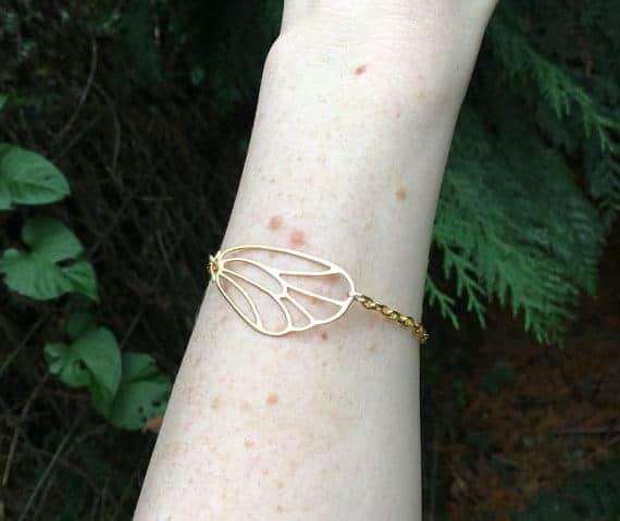 gold wing bracelet on arm