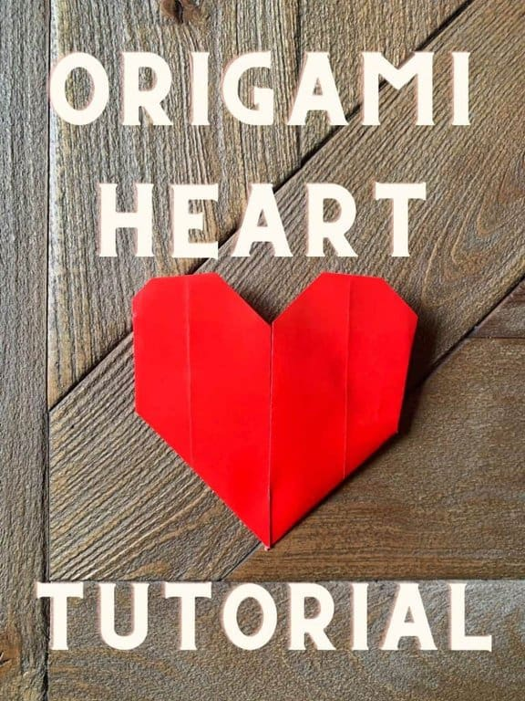 red origami heart on wood table with text over top.