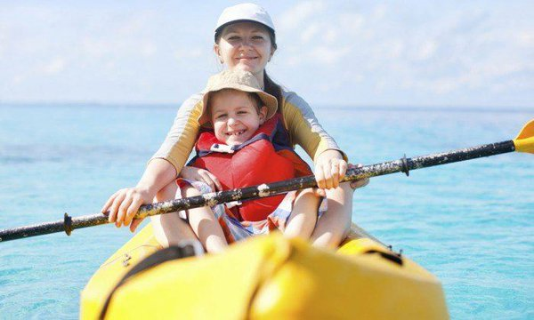 A single parent kayaking with her child in the caribbean sea off of riviera maya