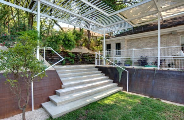 go for a modern landscape with white railings, metal pergola, and corten steel retaining walls