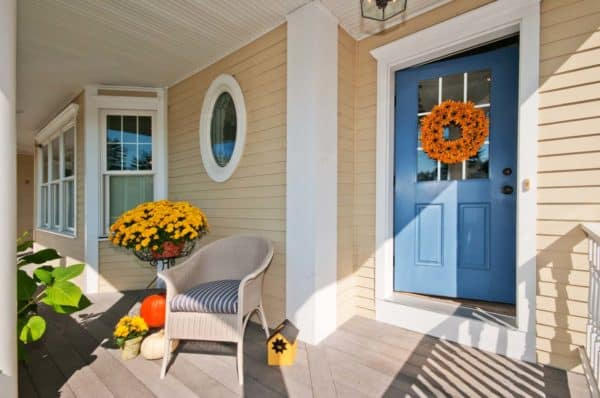carolina blue front door on a tan house for whimsical porch